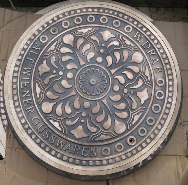verzierte Schachtabdeckung aus Bronzeguss